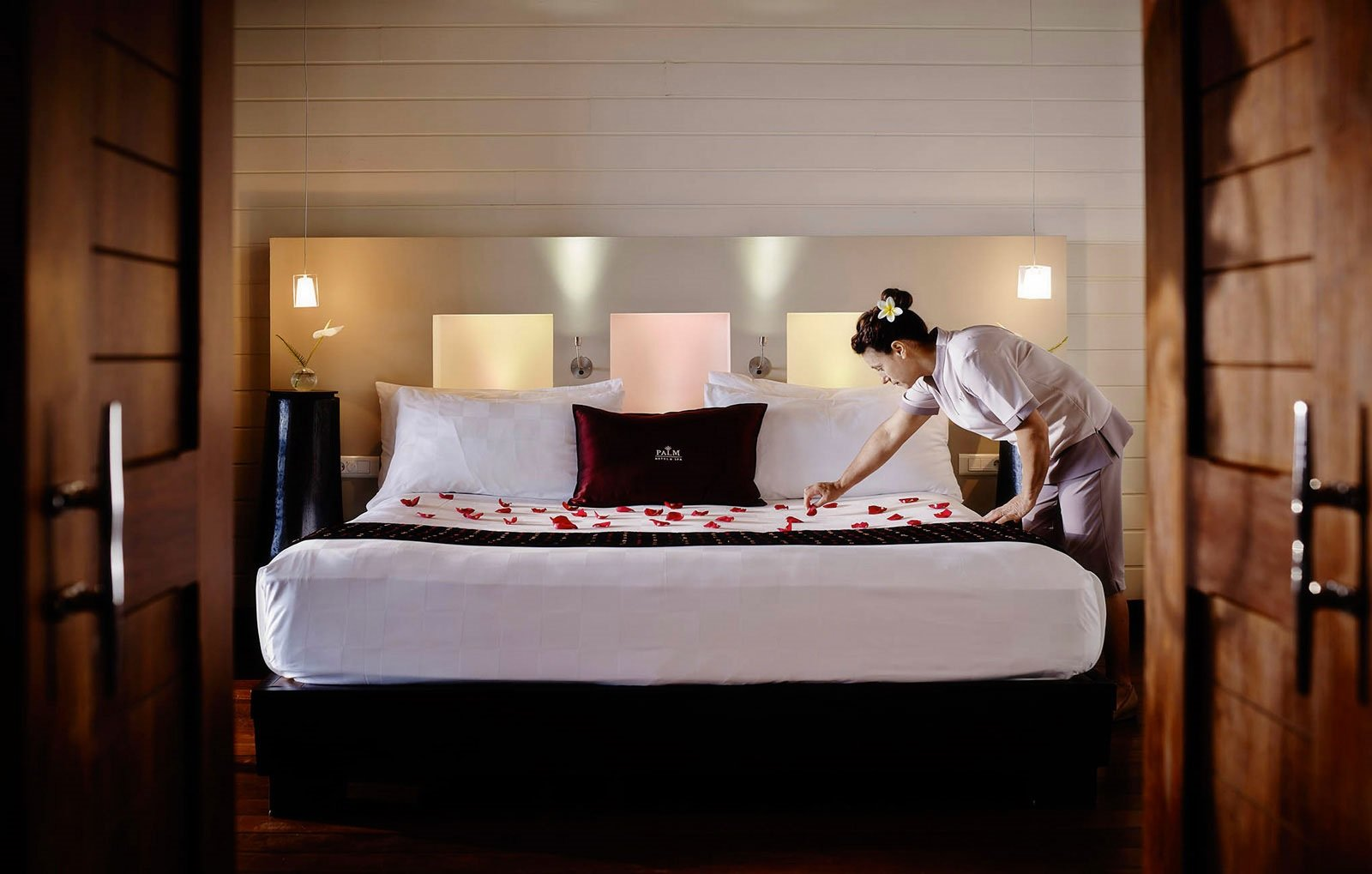 Hotel room with one bed and a house keeper placing rose petal