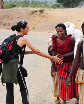Backpacking woman shaking hands with a group of people