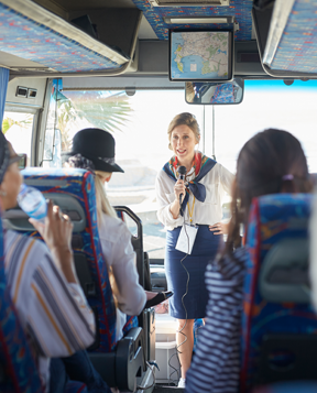 Woman tour guide on bus with tour group