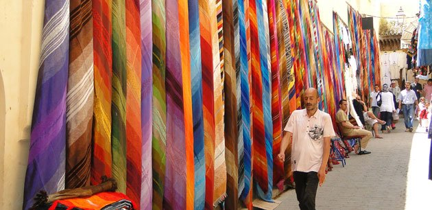 A wall covered with colorful cloths with men walking by